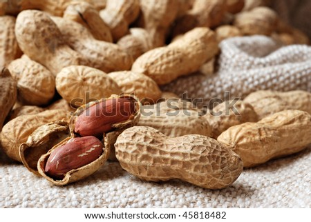 Peanuts arranged on hand woven cotton fabric.  Natural side lighting to emphasize texture.  Macro with extremely shallow dof.
