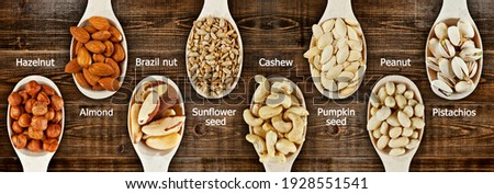 Peanuts, cashews, hazelnuts, almonds, Brazil nuts, sunflower seeds, pumpkin seeds, pistachios close up. Nuts in a wooden spoon on a brown board. Nuts on an old shabby table. Signed names of nuts.