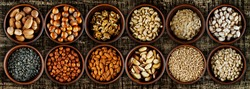 Peanuts, cashews, hazelnuts, almonds, walnuts, pecans, Brazil nuts, sunflower seeds, pumpkin seeds, pistachios close up. Nuts in clay bowls on a brown wooden board. Nuts on a shabby table.