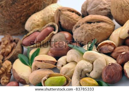 Peanuts, cashews, pistachio, almonds, walnuts, coconut, Brazil nuts and hazelnuts on a white background - stock photo