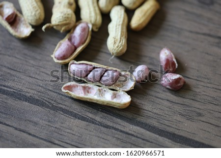 peanuts, groundnuts or monkey nuts put on a wood table background Snacks that are flavorful and useful.