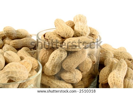 Peanuts in a clear glass and cups with more peanuts spilled around the glass isolated on a white background.