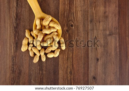 Peanuts in a wooden spoon on brown wooden background