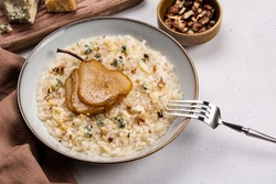 Pear and gorgonzola risotto with walnuts on white table. Ingredients on background. Copy space.