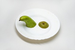 pear conference: green top and grayish rough bottom. pieces of sweet varietal fruit in small white plate