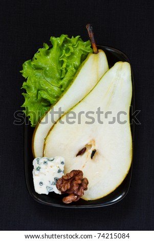 Pear with blue cheese, walnut and a leaf of green salad on a black background.