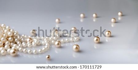pearl beads and pearls with reflection on gray background