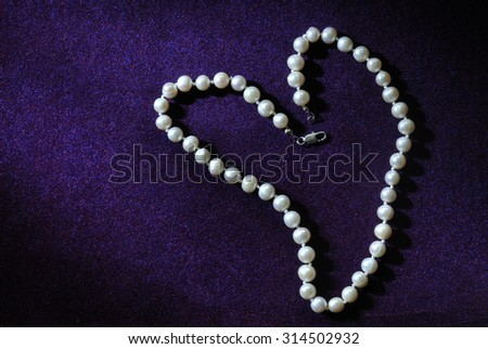 pearl beads in heart shape on purple velvet background #314502932