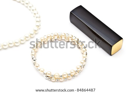 Pearl bracelet ,necklace and lipstick on white background