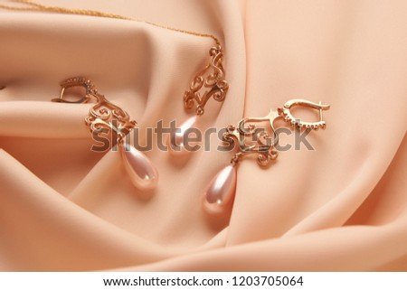 9c744ece6e3933 Pearl Golden Necklace and Earrings on beige silk background with copy  space. Beautiful precious women's