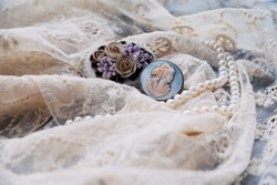 Pearl necklace and antique broches on old lace textile.