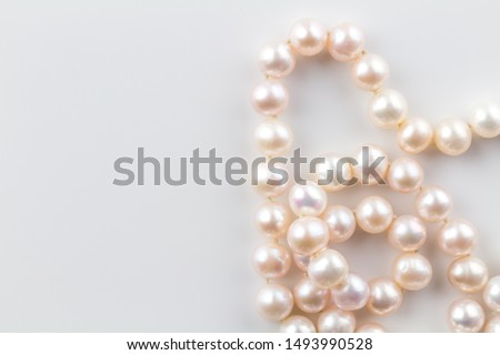 Pearl necklace background with a string of pink pearls isolated on white background - top view photograph ストックフォト ©