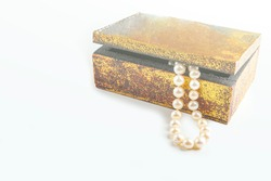 Pearl necklace, beads in antique metallic vintage casket on white background. Oldfashioned decoration from grandma's jewelry box.  Copy space, close-up, backlight