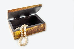 Pearl necklace, beads in antique metallic vintage casket on white background. Oldfashioned decoration from grandma's jewelry box.  Copy space, close-up