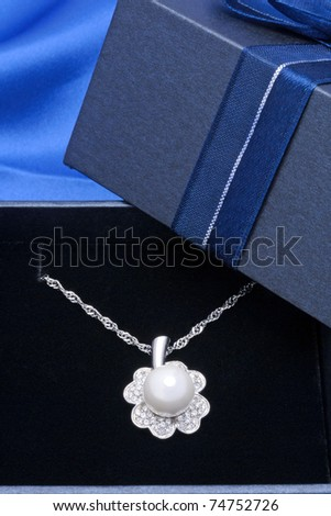 Pearl necklace in gift box isolated on  blue background