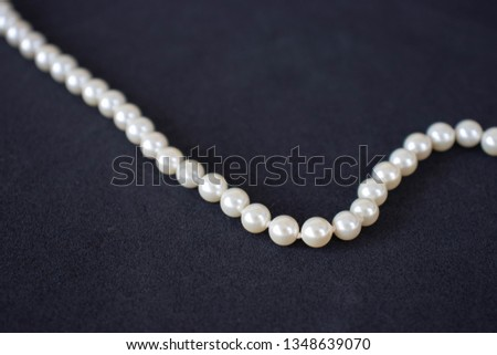 Pearl necklace on a black background #1348639070