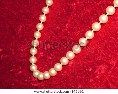 Pearl necklace on crushed velvet background