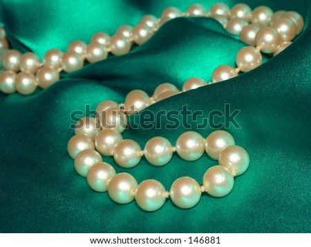 Pearl necklace on green satin background
