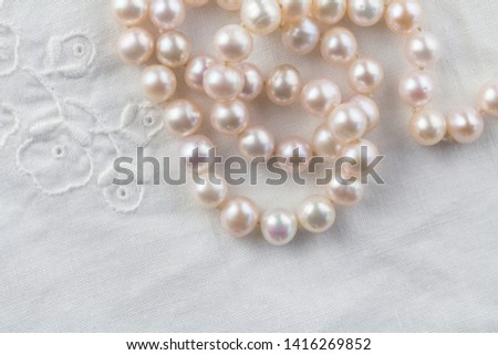 Pearl necklace on white embroidered linen background - top view photo of real pink pearls #1416269852