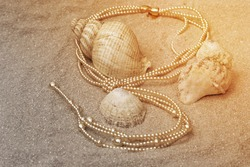Pearl necklace with gold clasp on a sandy beach with shells.  Luxury jewellery concept