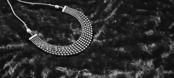 Pearls and stones silver necklace on dark black velvet background