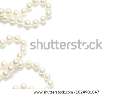 Pearls on a pearl necklace against a white background