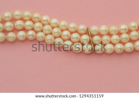 Pearls on pink background #1294351159