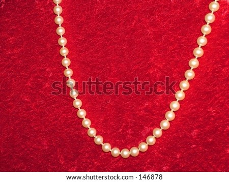 Pearls on red velvet background - stock photo