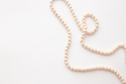 Pearls on white background with copy space. Necklace jewelry.