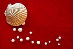 Pearls with golden shell on red velvet