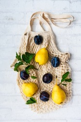 Pears and plums on a reusable shopping bag. Flat lay, autumn background.
