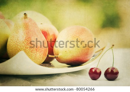 pears on a plate and two cherries with decorative texture