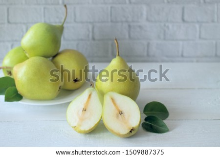 pears on white background. pears in a plate and on a wooden table. pear halves. #1509887375