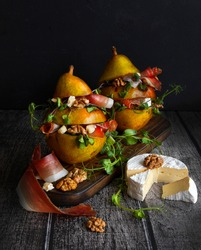 Pears stuffed with lettuce, cheese, jamon and walnuts. Salad with pears. An unusual pitch. Food styling