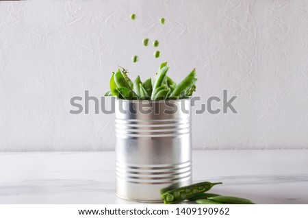 Peas falling into the tin can full of peas in pods.Canned peas in tin on the white table against white backgraund,empty space
