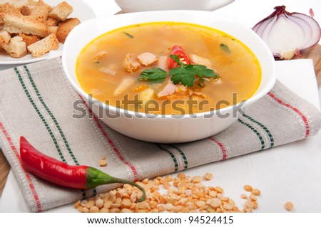 Peas soup in a porcelain plate with pepper