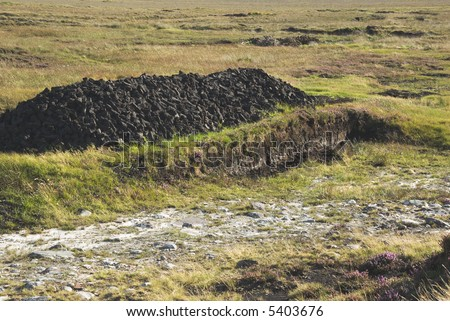 Peat bog in Achill Island, County Mayo, Ireland, showing a stack of turf cut to dry in the sun for fuel