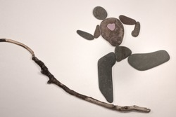 pebble art, pebbles, flat stones assembled to resemble the human form, conceptual, the shape of a person running hard up a hill, with heart shaped stone  on a path made from a twig to resemble a hill