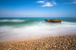 Pebble beach and silk effect in the Mediterranean Sea, rocks and foam with blue sky and clouds.