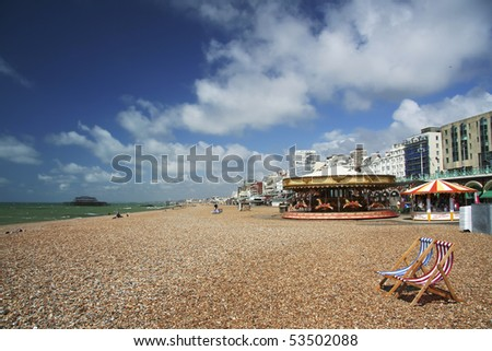 pebble beach with striped red and blue canvas deckchairs, brighton, england