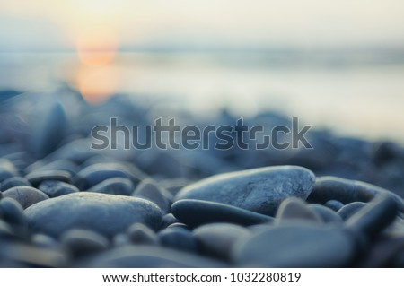 Photo of  Pebble stones on the shore close up in the blurry sunset light in the distance  background.