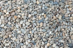 Pebbles background with dry leaves. Light color pebble rocks texture.