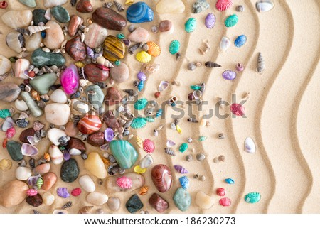 Pebbles, gemstones and shells scattered in a decorative arrangement on tropical golden beach sand with a ridged undulating wavy pattern in an ornamental nautical background