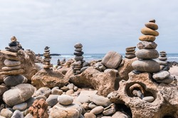 Pebbles heaped and balanced in a tower on top of mineral rocks in cityscape - Zen image of tranquility at Farol beach in Milfontes, Vicentine Coast Natural Park PORTUGAL