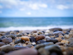 Pebbles on the beach close up on the sea surf background, copy space