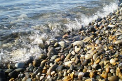 Pebbles on the beach washed by waves.Waves washing over empty gravel beach.Wet stones on the seashore. Glare, beach. summer, holidays, vacation, travel, nature, romantic getaway, tourism concept