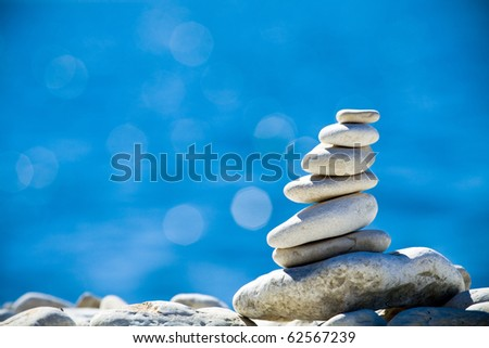 Pebbles stack balance over blue Adriatic sea in Croatia. Blue sky and water on sunny coast in summer.