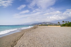 Pebbly beach in Motril Spain with azure coastal waters. Wide beach of southern Spain with mountains in a distance, clear water and partly cloudy blue sky.