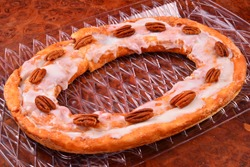 Pecan Kringle oval with pecans on top laying on a clear tray over a burl countertop.