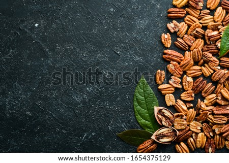 Pecan nut on black stone background. Assortment of pecans. Top preview. Free space for your text. Foto stock ©